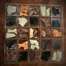 Dog treat advent calendar inside tray showing treat shapes and sizes