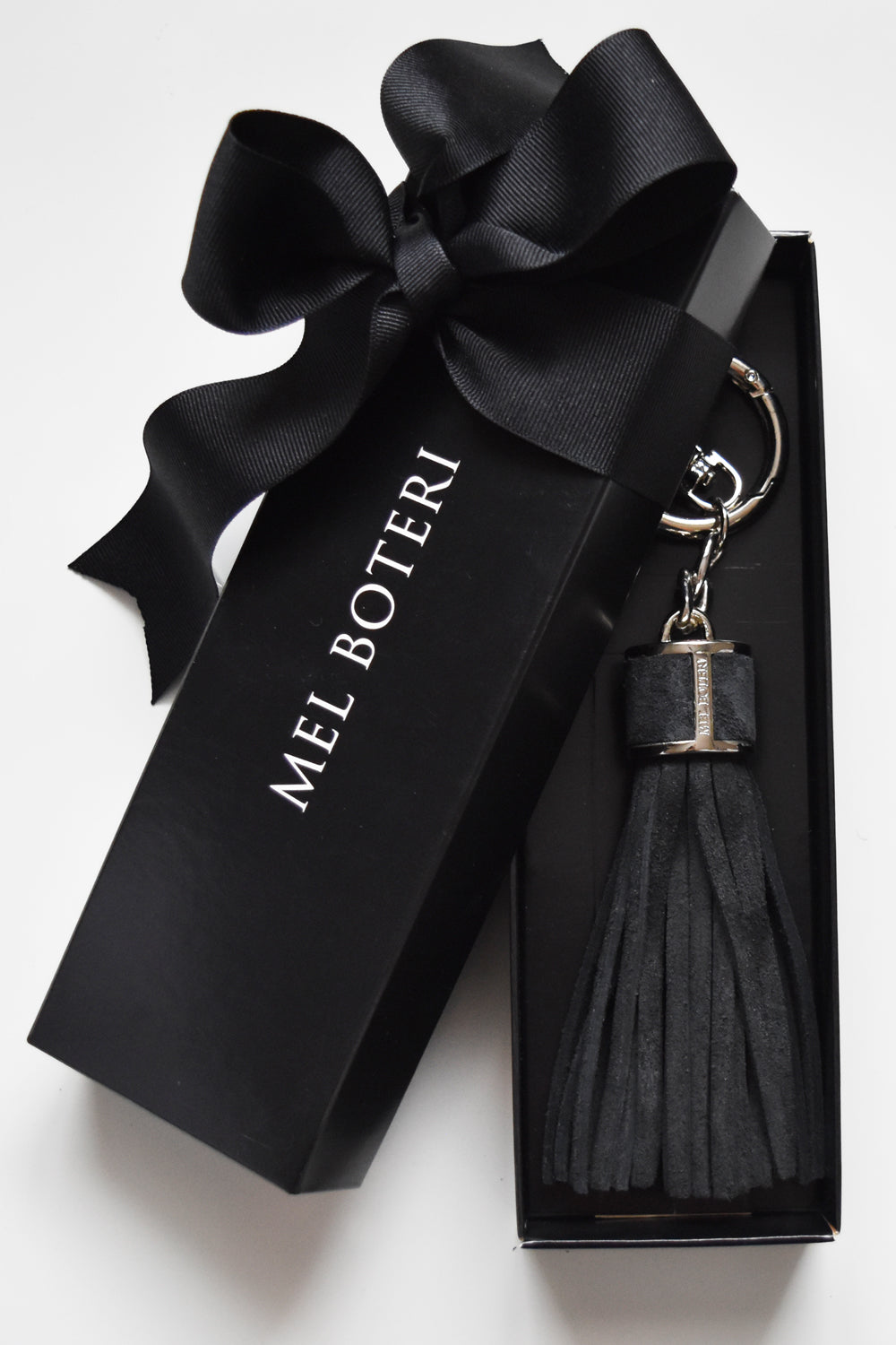 Mel Boteri | Charcoal Suede Leather Tassel Bag and Key Charm | Model