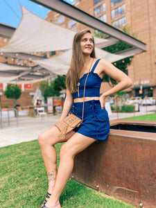 indigo colored two-piece set with ruffles. Shorts feature a cinched waist with ties.