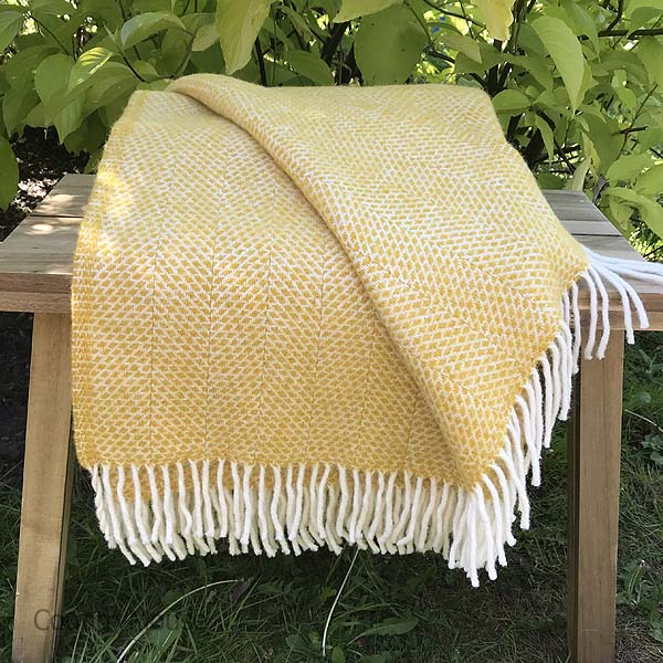 Country Mouse Yellow Beehive Pattern Wool Throw on a bench