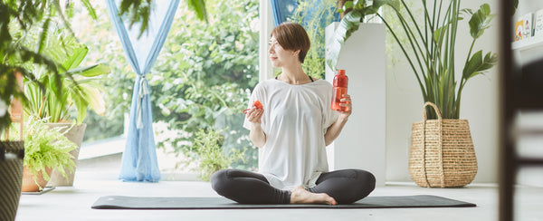KINTO Journal Article Yogi sitting with red WORKOUT bottle