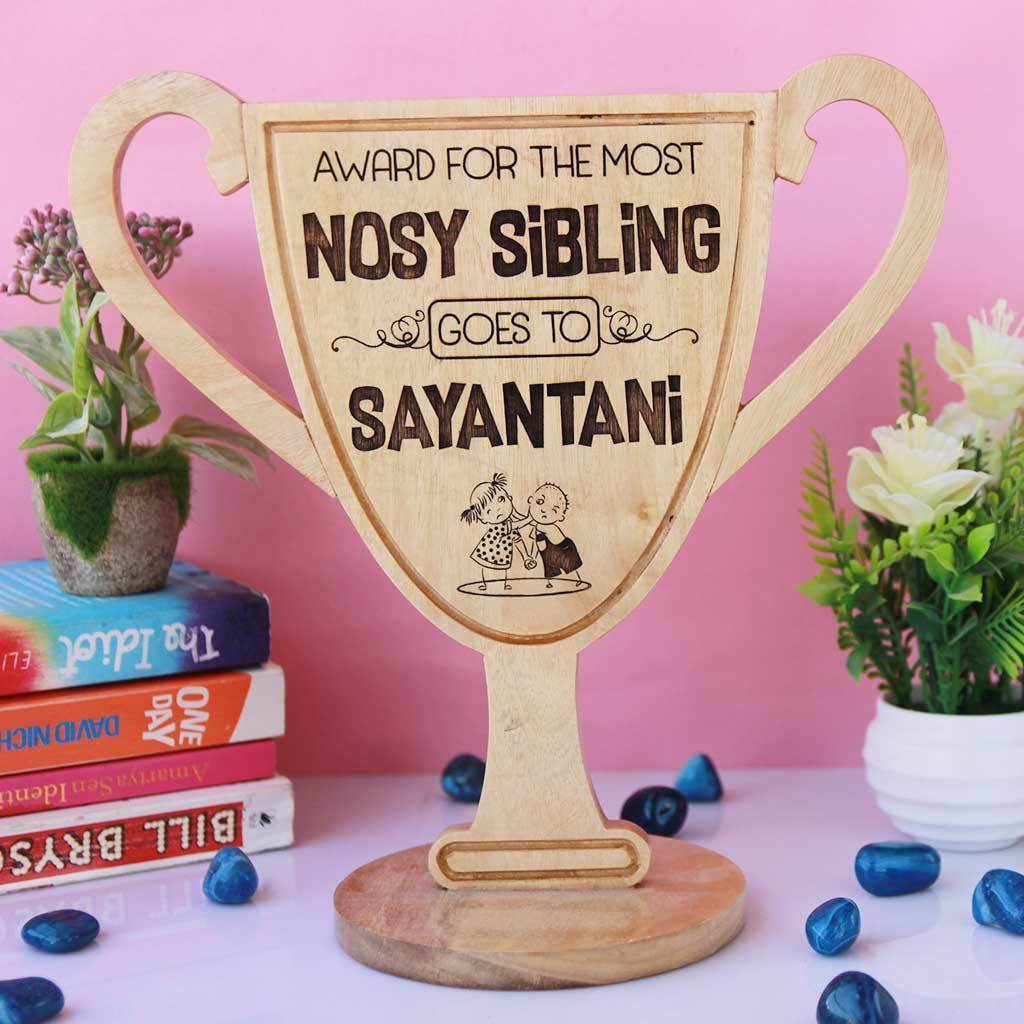 Most Nosy Sibling Wooden Trophy Cup. This funny award is one of the best gifts for sister and gifts for brother. Custom trophies can be personalized with your sibling's name.
