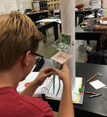 A student constructs a model deer stand at his desk using paper, colored pencils, and tape.