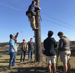 A person demonstrates to students the correct method for climbing a tree stand.