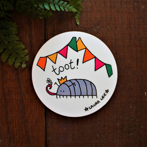Fun bug coaster high quality round wooden coaster Cyril the woodlouse at a party under colourful bunting wearing a party hat and blowing his tooter