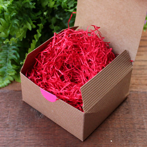Kraft gift box filled with red shred