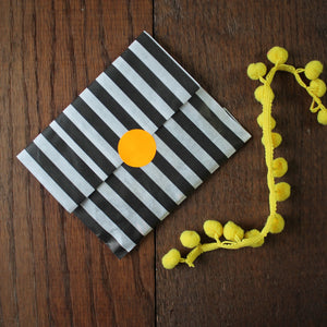 Black and white striped paper gift bag sealed with a neon orange round sticker gift bagged