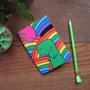 Rainbow dinosaur notebook by Laura Lee designs goofy dinosaurs on a background of rainbows