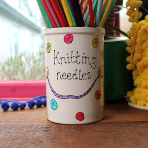 Scattered colourful buttons on a llama knitting needle storage jar
