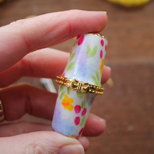 Floral sewing needle case with gold bow clasp hand painted in Cornwall by Laura Lee
