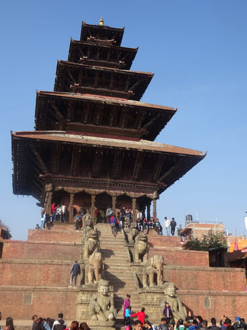 Temple at the top of steep steps surrounded by people with blue sky in the background