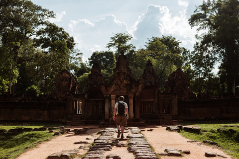 Man wearing rucksack walking towards Angkor Wat in Cambodia