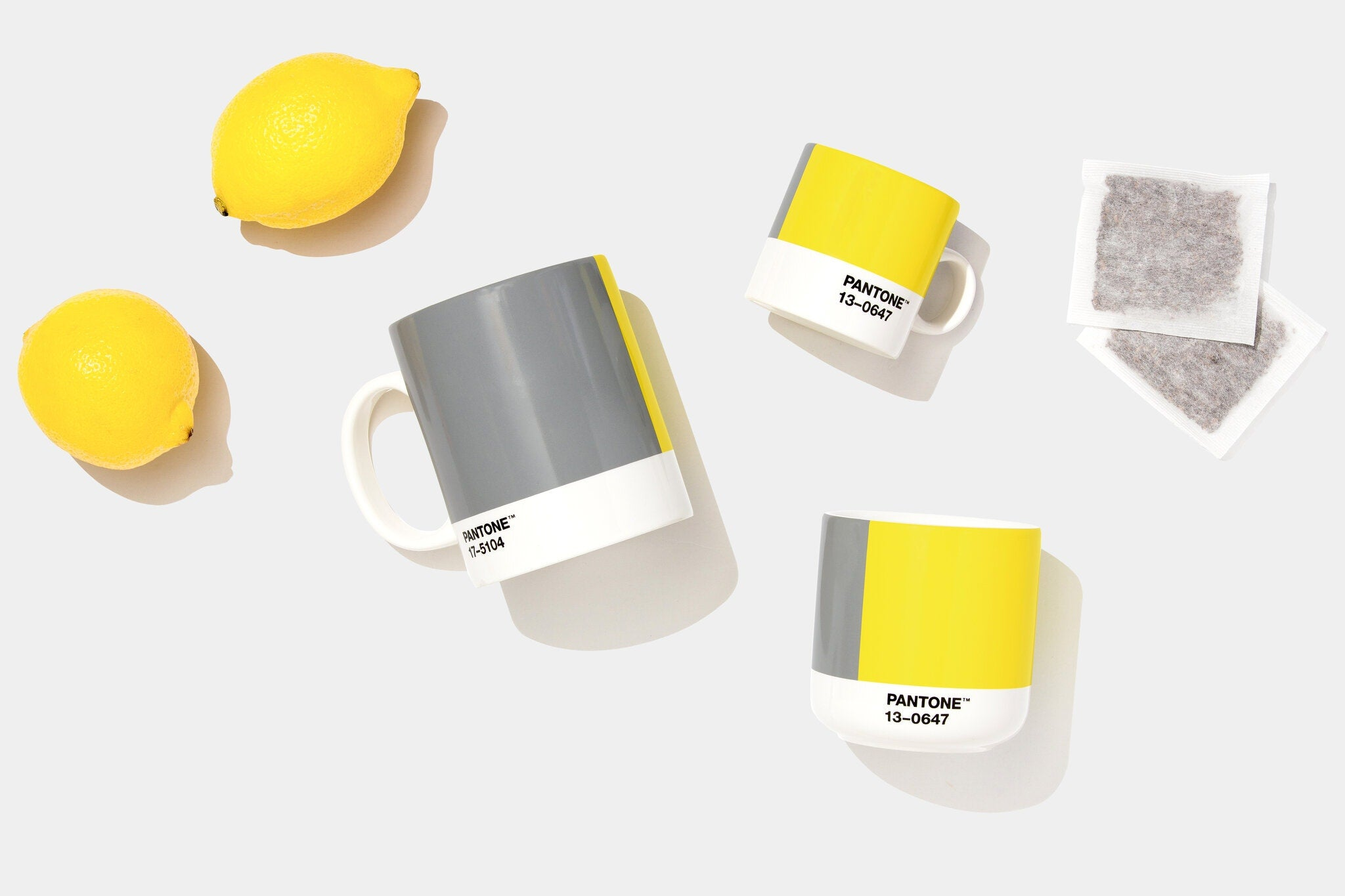 Mugs showing swatches of the Pantone Colors of the Year surrounded by lemons