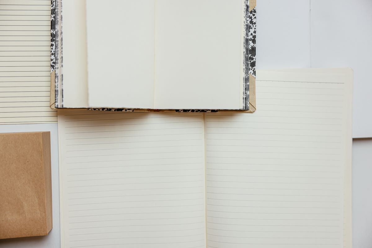 A collection of notebooks and paper sitting open on a desk