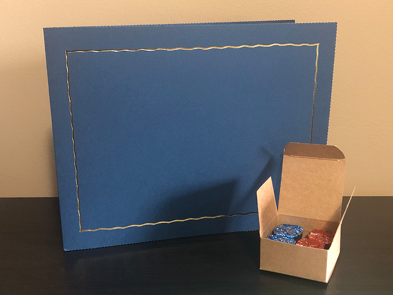 Blue atlas certificate holder with a kraft 4-piece favor holder with chocolate inside