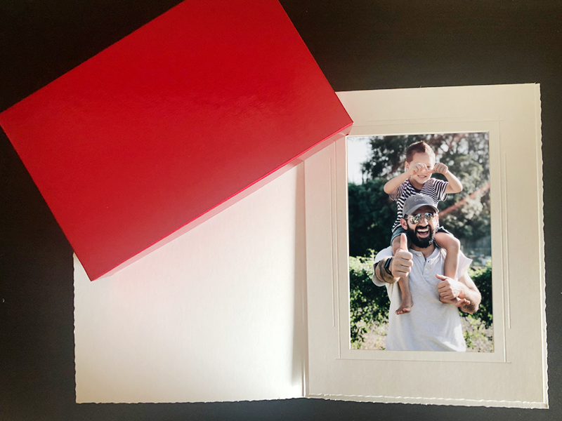 Red rigid candy box with a white capitol folder with a picture of a dad and son