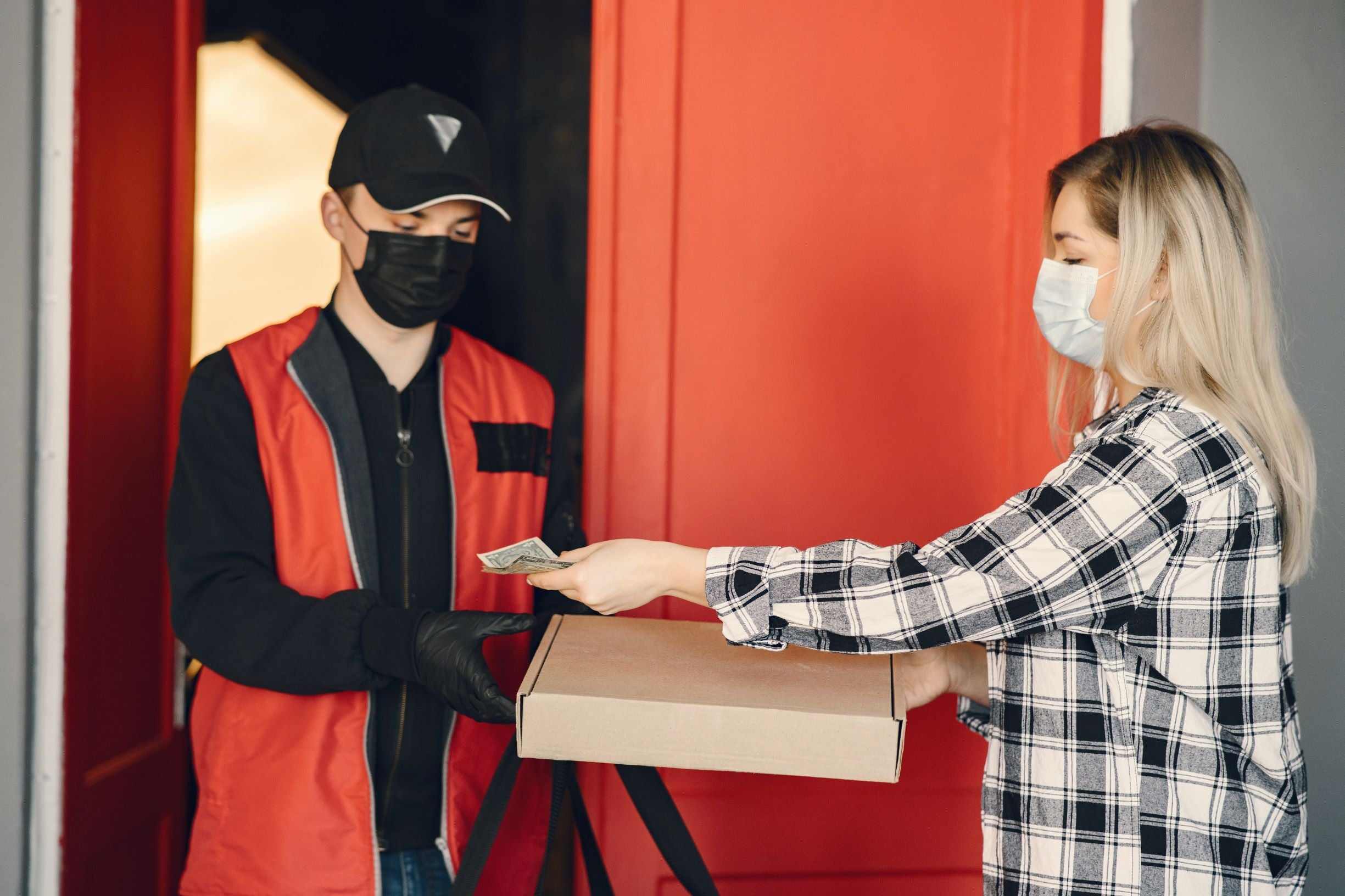 woman handing money over to a man for pizza and both are wearing face masks