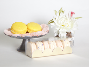 Two yellow macarons sit on top of a silver platform tray. Next to that are white flowers in a vase. In front is the 6 piece macaron box with gold tray. Box is filled with 6 macarons.