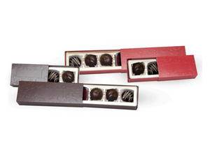 Red and brown two piece and four piece embossed truffle slides with slides pulled out showing chocolate