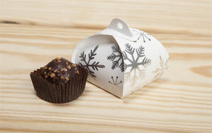 A Let It Snow single truffle tote sitting on a wooden table next to a chocolate truffle