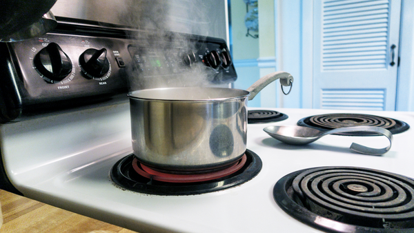 pot of water boiling on stove with steam coming out