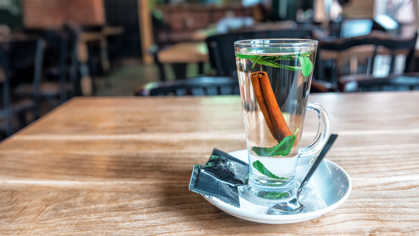 warm tea with cinnamon stick and mint leaves