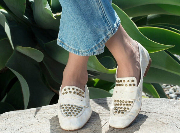 woman wearing handmade white gold leather loafer for women with brass studs artwork
