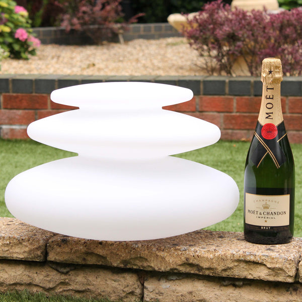 A spiral shaped outdoor lamp, 25 cm high, next to a champagne bottle