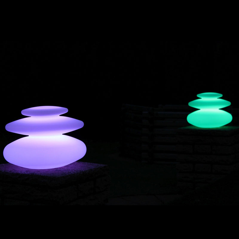 Two spiral mood lamps, set to purple and green, at night