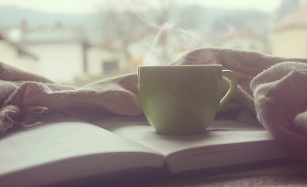 Teacup Placed On Book, Surrounded by Cozy Blankets