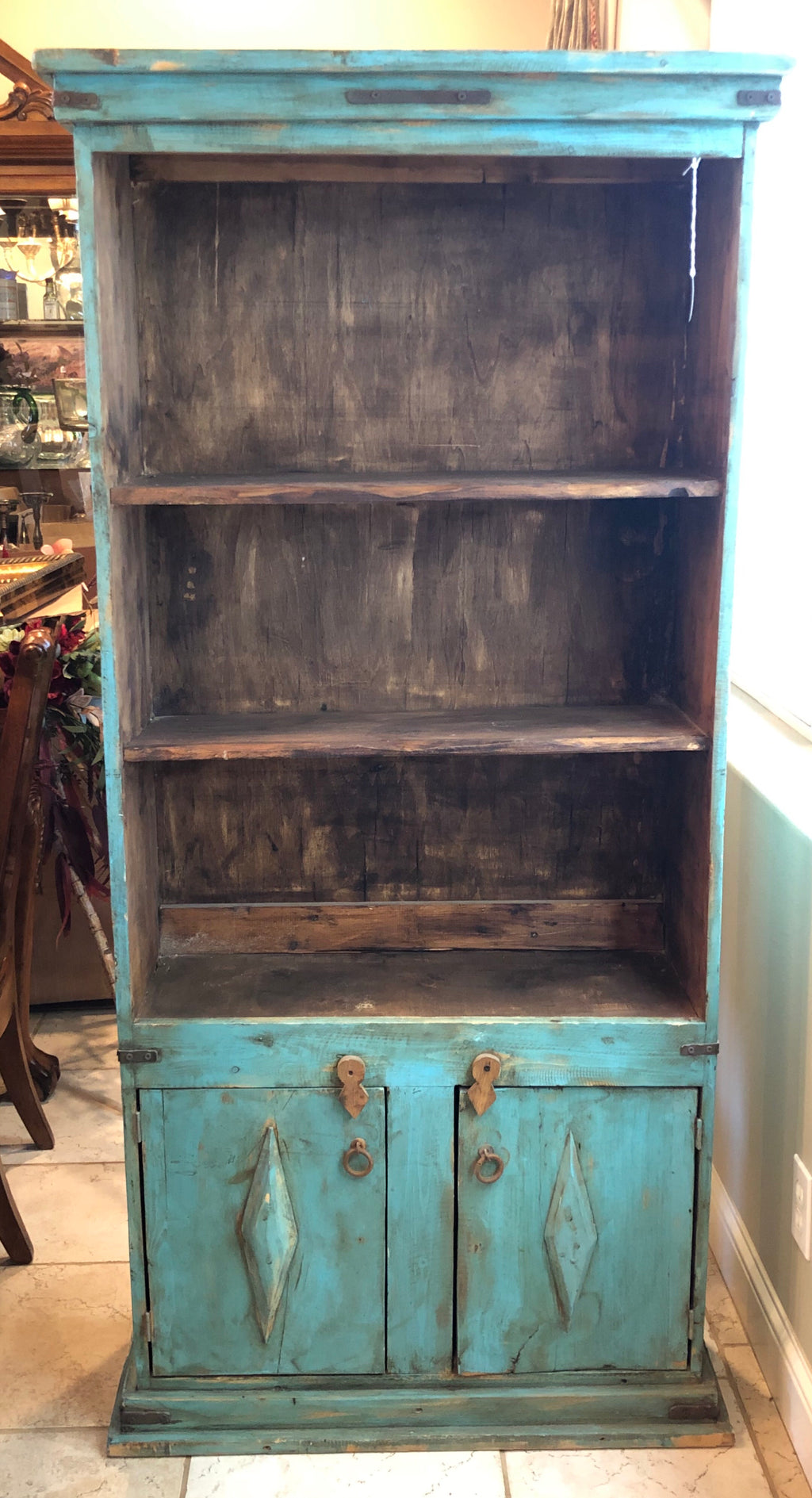 Turquoise and brown three shelf bookshelf with cabinet