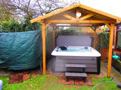 white and grey hot tub under a wooden gazebo
