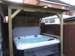 white hot tub filled with water under wooden gazebo