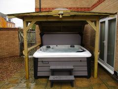 hot tub within wooden gazebo next to house