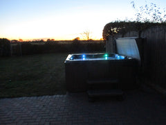 Hot Tub with lights on and sunset in background