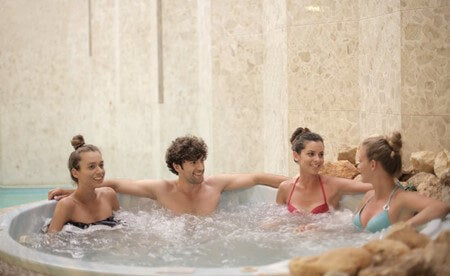 a group of friends sat in a hot tub smiling