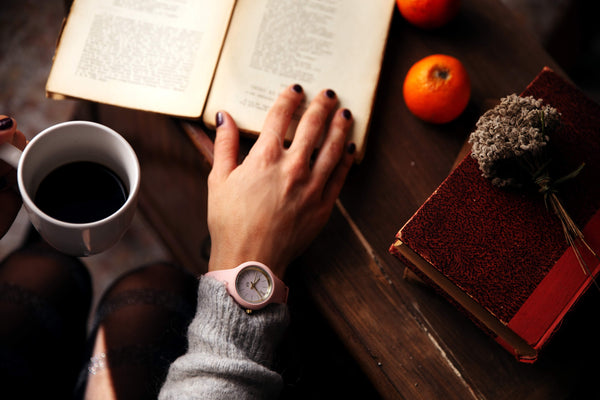 hand wearing a watch with a coffee cup and book