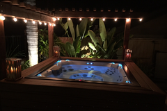 Hot tub on a night with fairy lights and blue lights in water