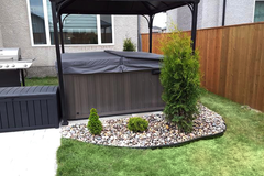 Hot tub with black cover and gazebo in garden