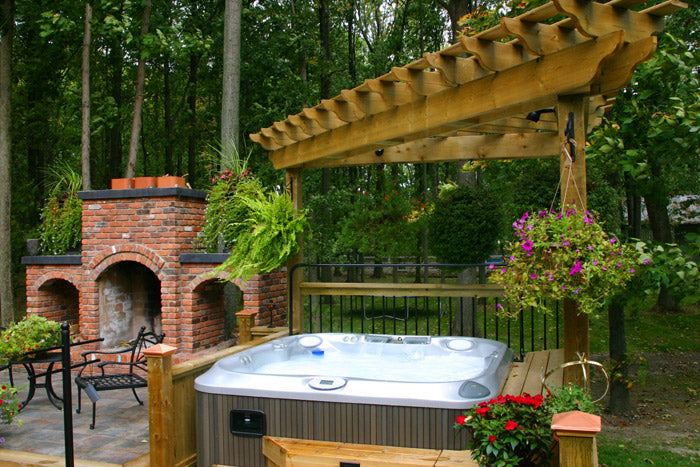 A Jacuzzi hot tub with a fireplace next to it