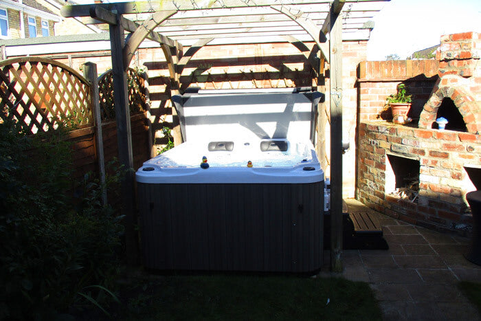 A Jacuzzi hot tub in a small garden