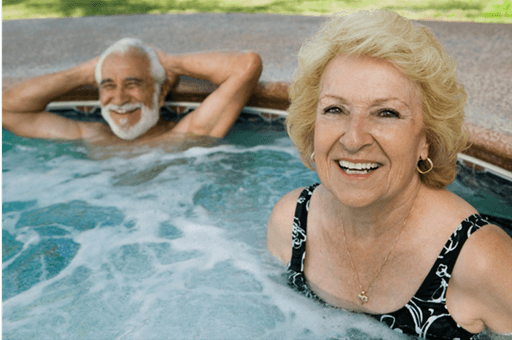old man and woman smiling in a hot tub