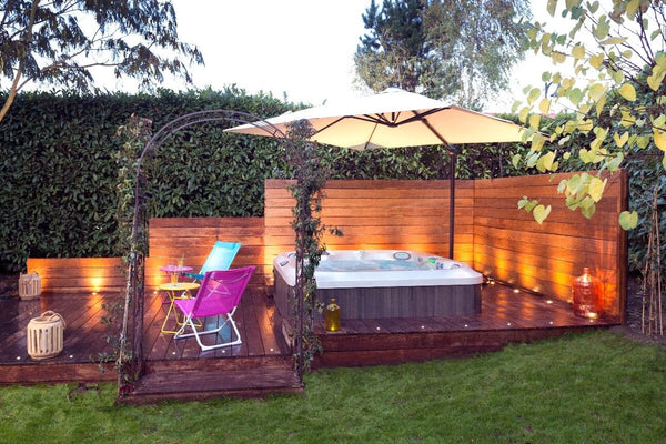 outdoor living lifestyle image of a hot tub in a garden with a canopy over