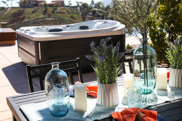 outdoor living lifestyle image of an outside table with drinks and flowers and a hot tub in the background