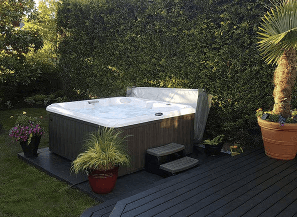 outdoor living hot tub outside on grass surrounded by plants