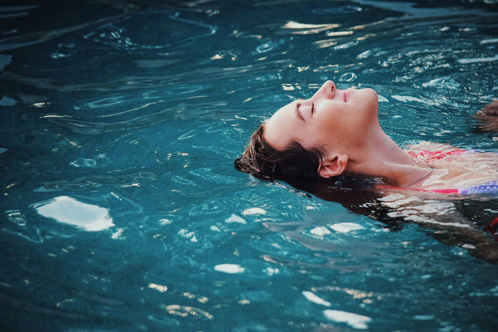 woman laying on her back floating in a pool