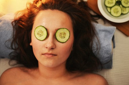 woman laying down with cucumber on her eyes