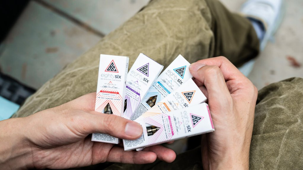Person holding Eighty Six vape cartridge boxes