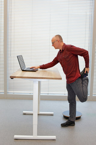 Photo of a middle-aged man in eyeglasses men with laptop at the mobile table doing the leg exercise