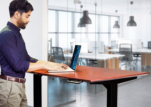 A person at a standing desk and looking at a computer